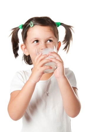 Happy little girl drinking a glass of milk isolated on white background photo