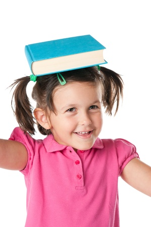 Smiling happy little girl with a book on her head isolated on white background photo