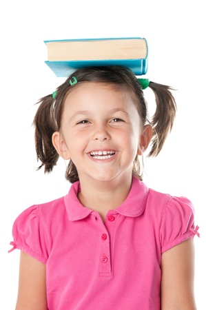 Happy smiling little girl carrying a book on her head isolated on white background photo