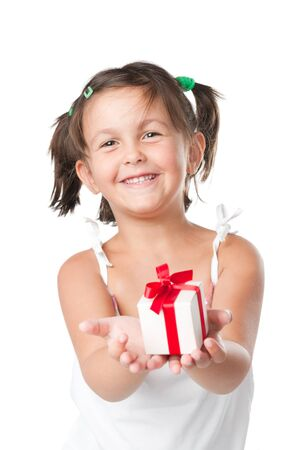 Happy smiling little girl holding and offering a gift for Christmas and birthday isolated on white background photo