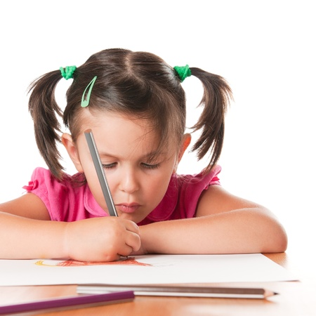 Absorbed little girl drawing with pencils isolated on white background photo