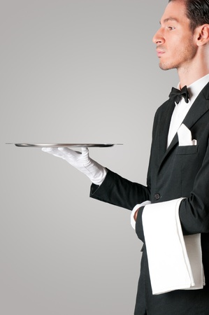 trays: Proud waiter holding an empty tray to place your product Stock Photo