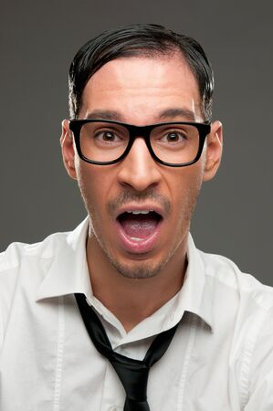 Shocked nerd with open mouth looking at camera Stock Photo - 8590281