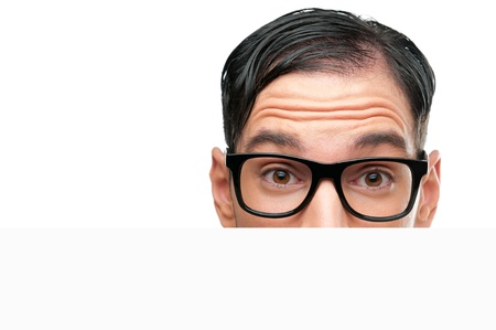 Close up of surprised nerd behind a white sign board isolated on white background photo