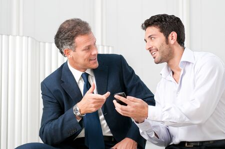 Two businessmen discussing together on a news on a smart phone Stock Photo - 8590041