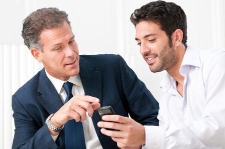 phone message: Two businessmen discussing together on a news on a smart phone Stock Photo