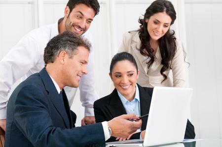 discutere: Happy business team di discutere insieme a office meeting con il portatile Archivio Fotografico