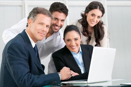 Satisfied proud businss team looking at camera and smiling in office Stock Photo - 8590255