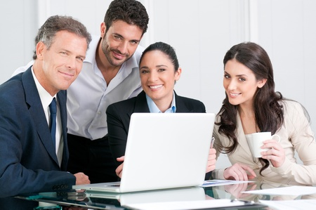 Satisfied proud businss team looking at camera and smiling in office Stock Photo - 8590067