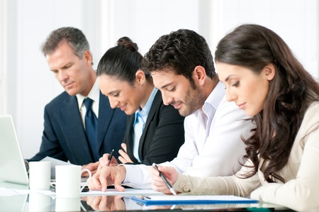 absorbed: Absorbed business team working together in modern office Stock Photo