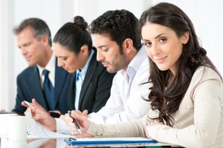 reunion de trabajo: Satisfecho mujer de negocios sonrientes mirando la c�mara con los colegas de trabajo de Oficina