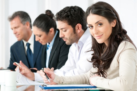 working: Satisfied smiling business woman looking at camera with working colleagues in office
