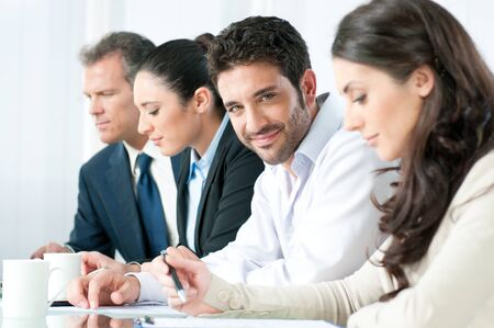 hispanic male: Smiling proud business man looking at camera with satisfaction and working colleagues in office Stock Photo