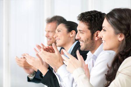 manos aplaudiendo: Feliz equipo de negocios sonriente Palmas de las manos durante una reuni�n en la Oficina Foto de archivo