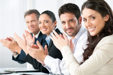 people clapping: Satisfied proud business team clapping hands and looking at camera in a modern office