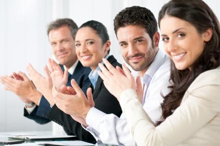 Soddisfatti orgoglioso business team battendo le mani e rivolto in un moderno ufficio