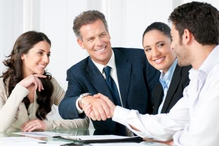 dandose la mano: Empresario maduro estrechar la mano para sellar un acuerdo con su socio y colegas en una oficina moderna