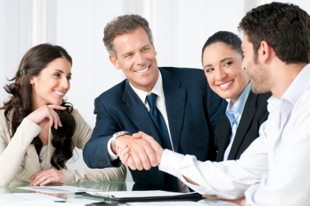 handskakning: Mature businessman shaking hands to seal a deal with his partner and colleagues in a modern office