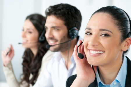 Beautiful young lady talking on headset at call center office photo