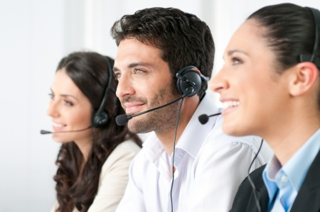 contact center: Smiling positive young man with headset and colleagues in a modern call center office Stock Photo