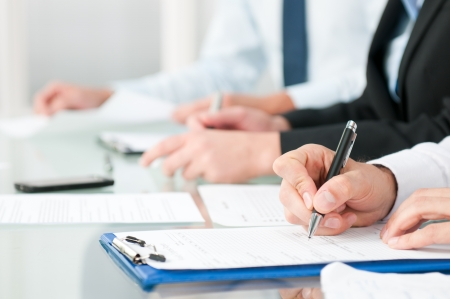 Close up shot of people compiling forms during a business conference photo