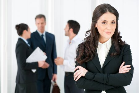 Smiling confident business woman looking at camera with her colleagues in background at office photo