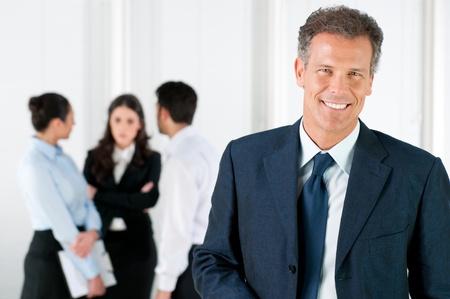 lideres: Empresario maduro moderno sonriendo y mirando la c�mara con sus colegas en segundo plano en Oficina