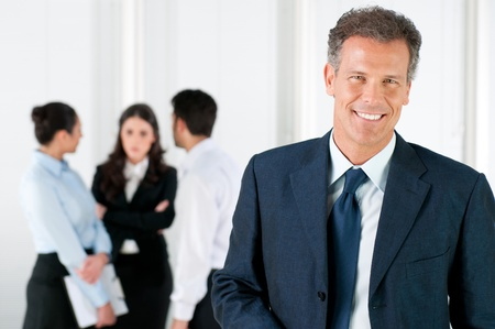 Modern mature businessman smiling and looking at camera with his colleagues in the background at office Stock Photo