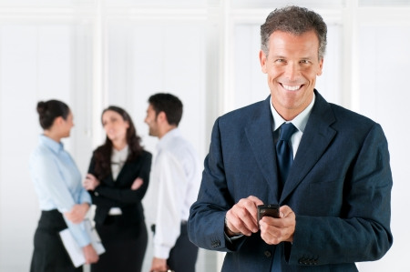 company manager: Happy smiling mature businessman receveing positive news on his smart phone at office