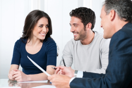 Financial consultant presents bank investments to a young couple Stock Photo - 8590254