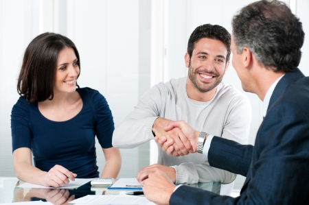 financial advice: Happy couple seal a deal with their personal financial advisor at home Stock Photo