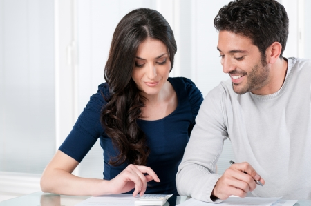 Happy smiling couple calculating their financial investments at home photo