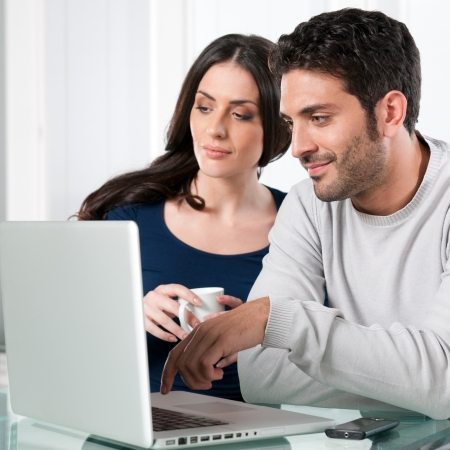 Smiling beautiful young couple surfing the net with laptop at home photo