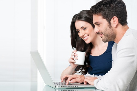 Happy modern couple surfing the net and working on laptop at home photo