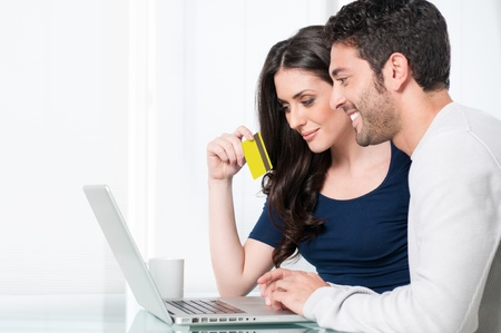 Smiling satisfied couple buying online with credit card at home photo