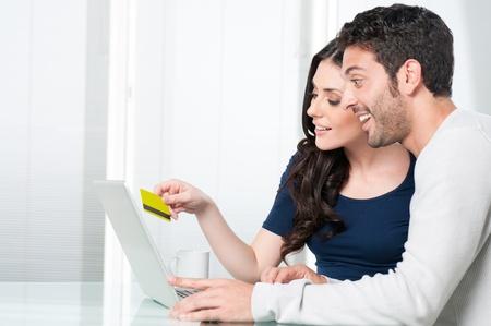 Gelukkige paar verbaasd op zoek- en koop online met credit card thuis Stockfoto