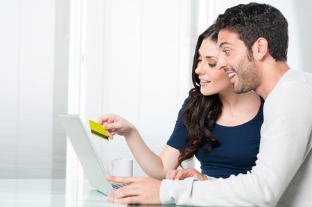 internet shopping: Happy surprised couple looking and buying online with credit card at home