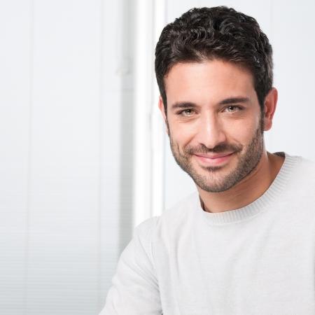bel homme: Happy guy souriant, regardant la cam�ra avec satisfaction Banque d'images