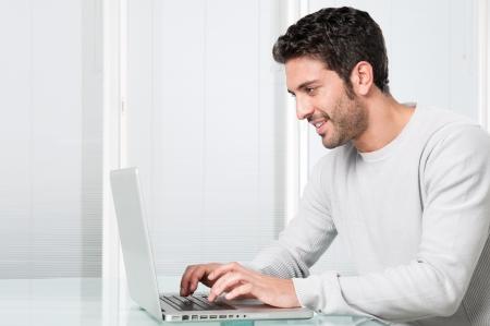 business man laptop: Feliz sonriente joven trabajando y escribiendo en el ordenador port�til en casa Foto de archivo