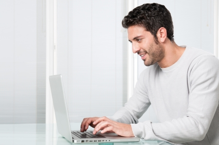 Happy smiling young man working and typing on laptop at home Stock Photo - 8590018