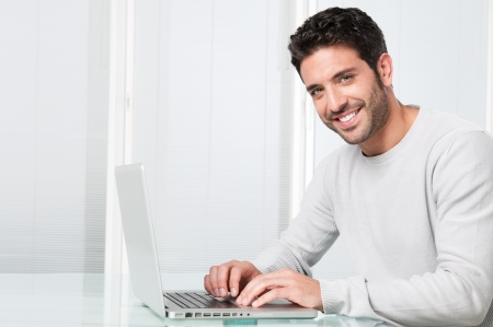 Happy satisfied young man working on laptop and looking at camera photo