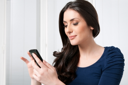 smart home: Young beautiful brunette lady touching and browsing her smart phone at home