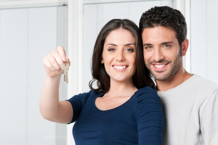 house keys: Happy smiling young couple showing a pair of keys of their new house Stock Photo