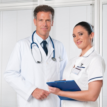 male nurse: Mature doctor and his female assistant smiling together at hospital