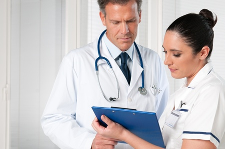 Doctor and nurse discussing together on medical exam at hospital photo