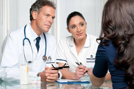 Jungen Patientin mit Ärzten diskutieren, auf ihre ärztliche Untersuchung im Krankenhaus