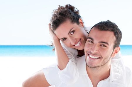 parejas jovenes: Pareja joven sonriente incluirse en playa hermosa de verano