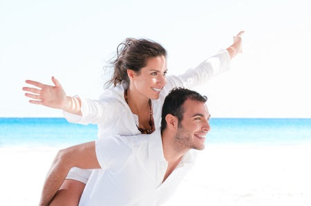 man carrying woman: Happy smiling summer couple piggyback together with arms outstretched at beautiful beach