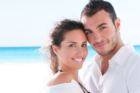parejas enamoradas: Sonriendo la feliz pareja mirando la c�mara juntos en la playa de verano