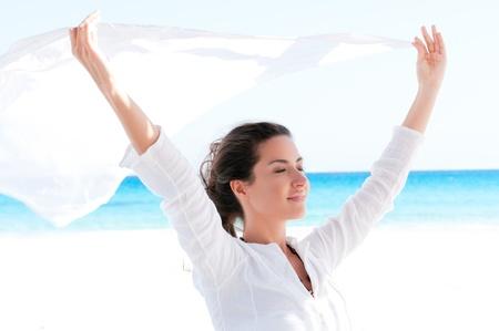 Hermosa joven celebración de tejido blanco al viento en unas vacaciones de verano